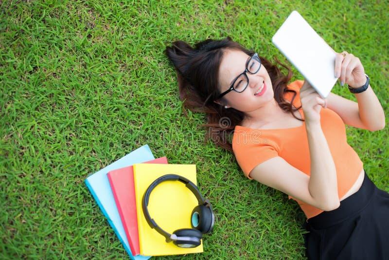 Femme s'étendant sur l'herbe et à l'aide du comprimé, concept d'éducation, concept de technologie photos libres de droits