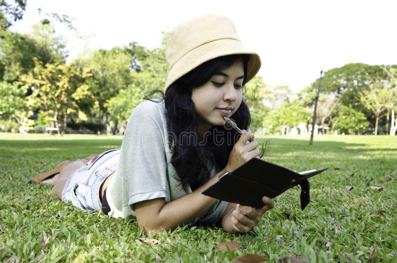 Femme s'étendant sur l'herbe et pensant en stationnement photos stock