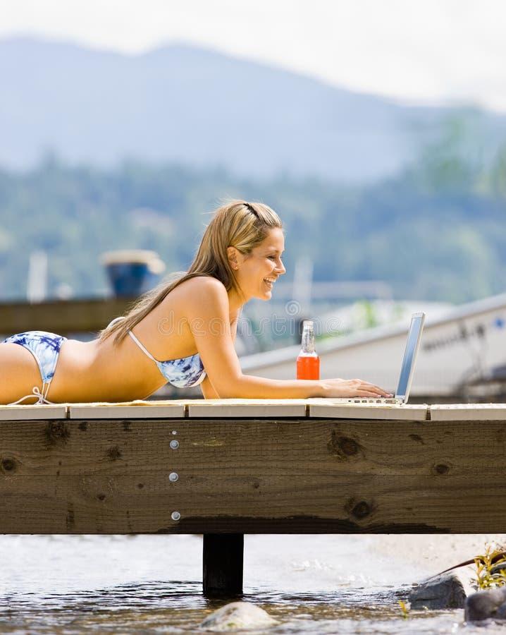 Femme s'étendant sur le pilier sur l'ordinateur portatif images stock