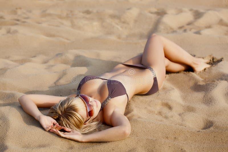 Femme s'étendant sur le sable image libre de droits