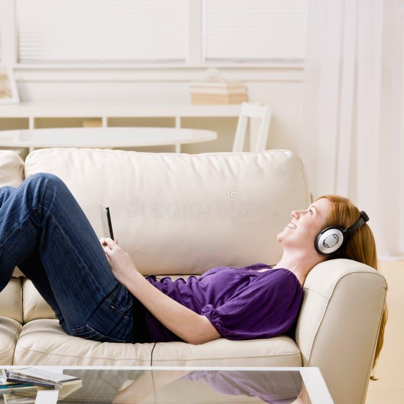 Femme s'étendant sur le sofa, écoutant la musique images stock