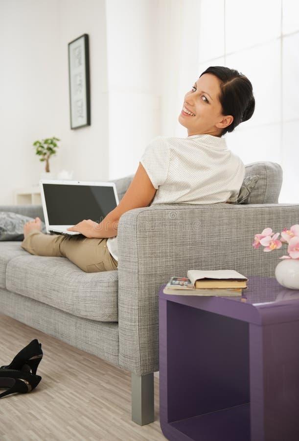 Femme s'étendant sur le sofa et à l'aide de l'ordinateur portatif. Vue arrière images libres de droits