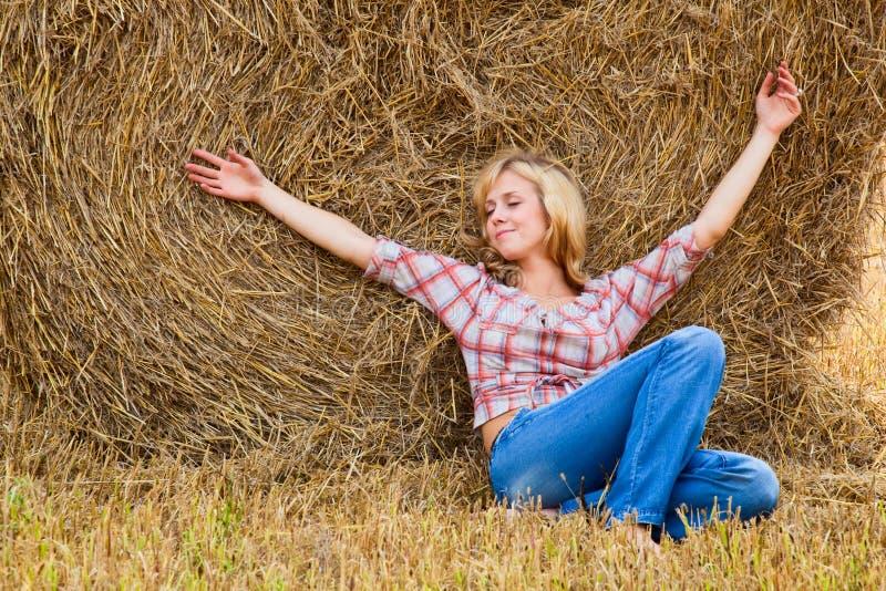 Femme s'étendant sur une paille photo stock