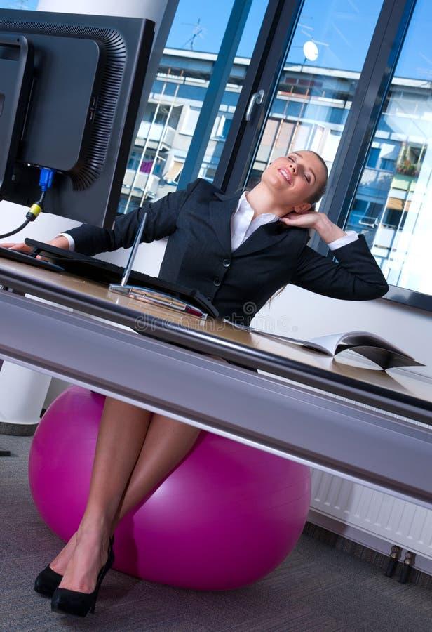 Femme s'étirant dans le bureau photo libre de droits