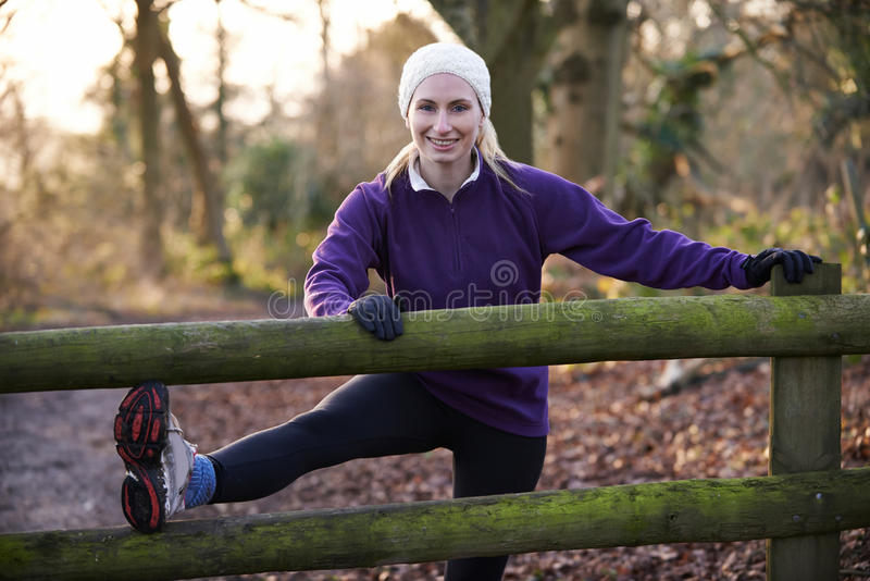 Femme s'étirant sur la course par la région boisée d'hiver photos libres de droits