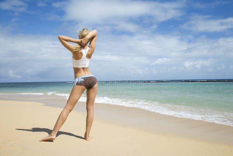 Femme s'étirant sur la plage. photo stock