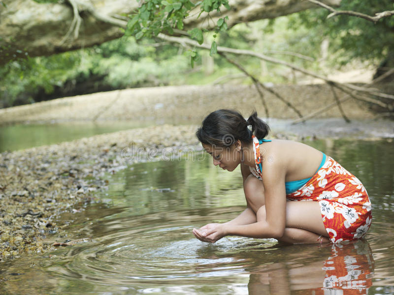 Femme s'accroupissant en Forest Lake With Hands Cupped images stock