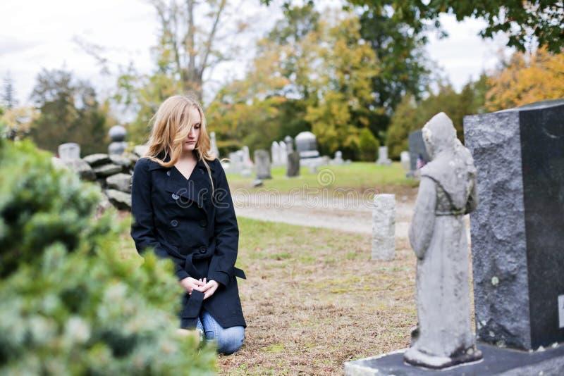 Femme s'affligeant dans le cimetière images libres de droits