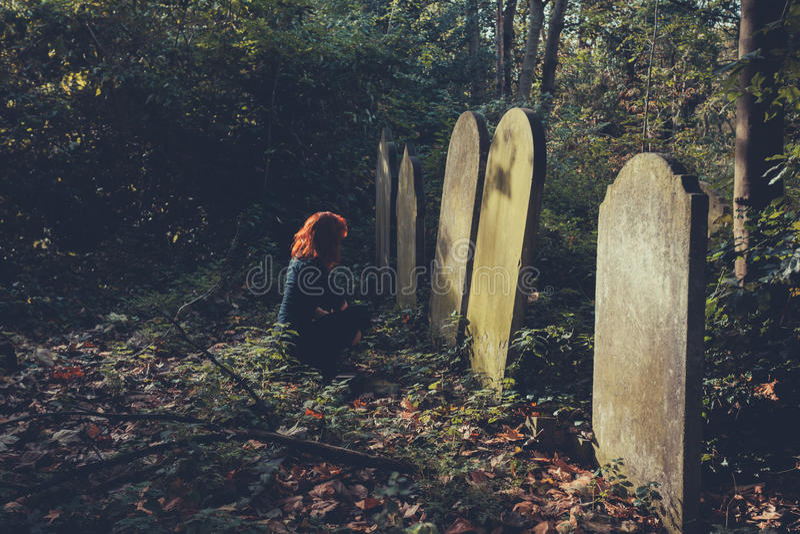 Femme s'affligeante par la tombe photo stock