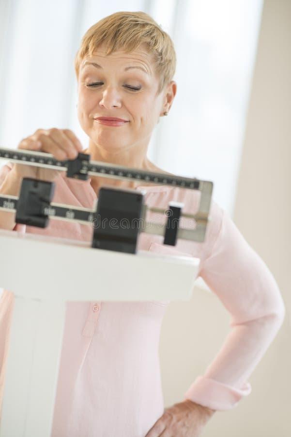Femme s'ajustant glissant l'échelle de poids image stock