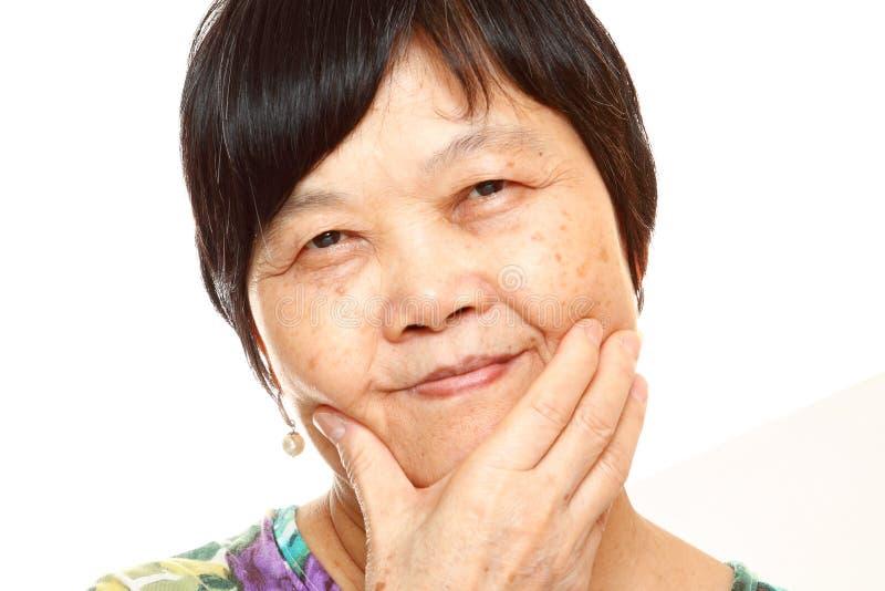Femme 60s asiatique supérieure heureuse image libre de droits