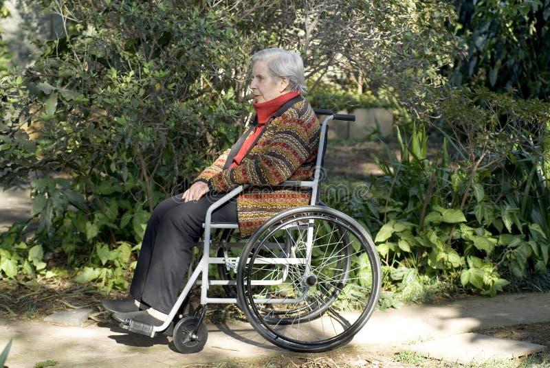 Femme s'asseyant à l'extérieur dans le fauteuil roulant - horizontal photos libres de droits