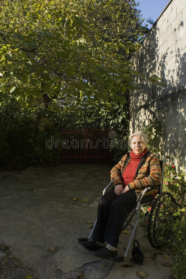 Femme s'asseyant à l'extérieur dans le fauteuil roulant - verticale image libre de droits