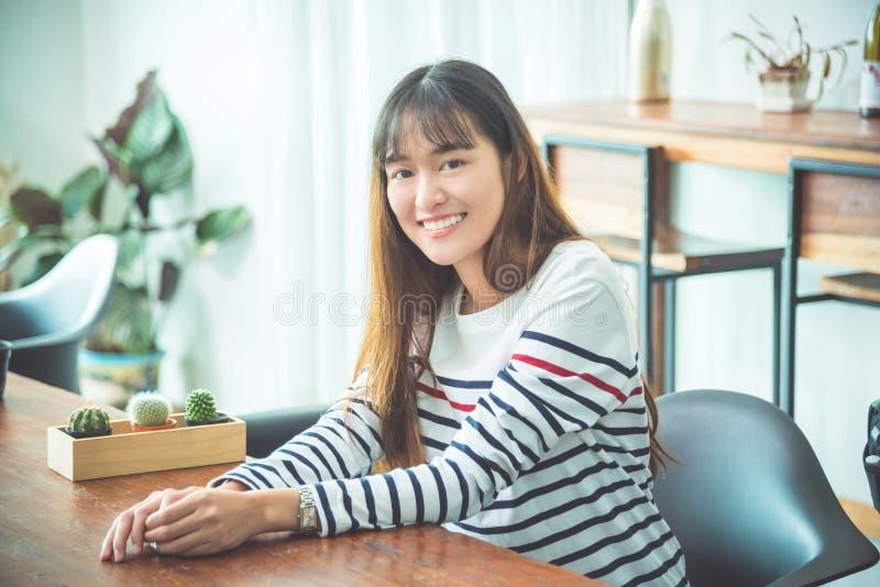 Femme s'asseyant à la maison et souriant à l'appareil-photo images stock