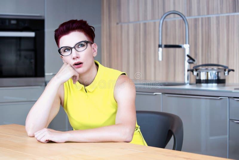 Femme s'asseyant à la table de cuisine semblant bouleversée image libre de droits