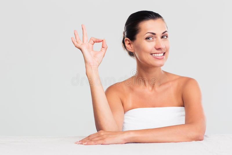 Femme s'asseyant à la table en serviette et montrant le signe correct images libres de droits