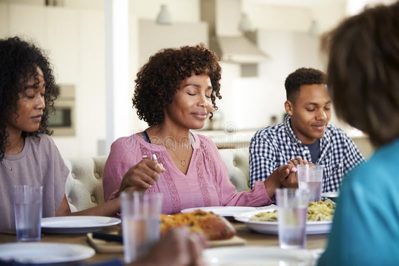 Femme s'asseyant à la table tenant des mains avec ses jeunes enfants adultes disant la grâce avant dîner image libre de droits
