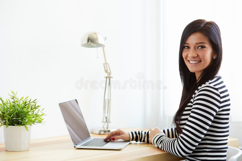 Femme s'asseyant à son bureau fonctionnant avec l'ordinateur portable photo stock