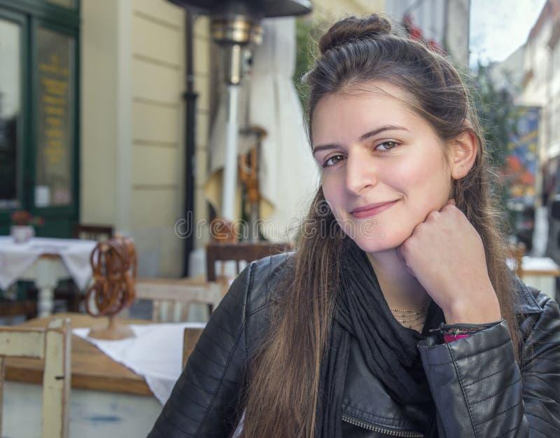 Femme s'asseyant au café extérieur photos stock