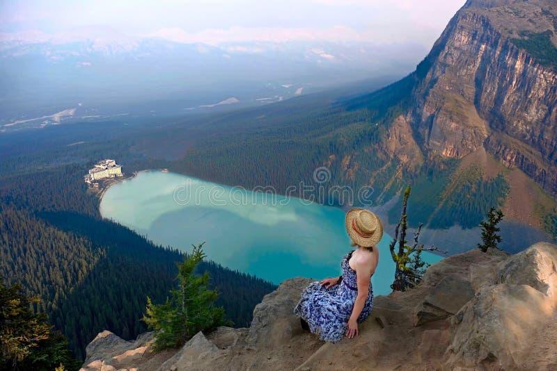 Femme s'asseyant au-dessus de Lake Louise avec la belle vue du château images libres de droits