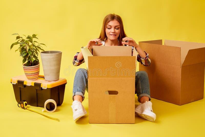 Femme s'asseyant au milieu des boîtes mobiles Les gens d?pla?ant le nouveau concept d'endroit et de r?paration Fond jaune photo libre de droits