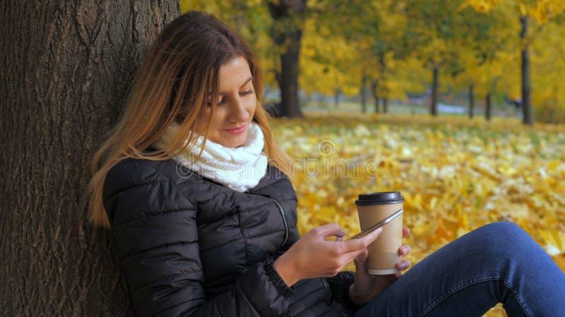 Femme s'asseyant avec elle de nouveau à l'arbre dans Autumn Leaves jaune, utilisations Smartphone photo stock
