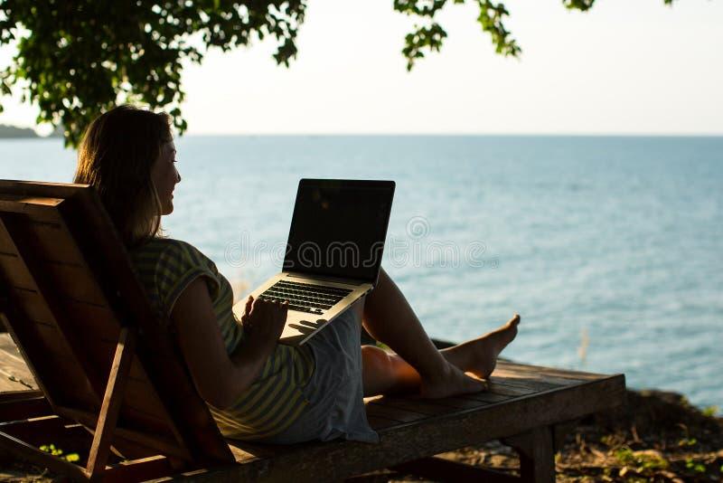 Femme s'asseyant avec l'ordinateur portable sur la chaise de plate-forme par la mer photo stock