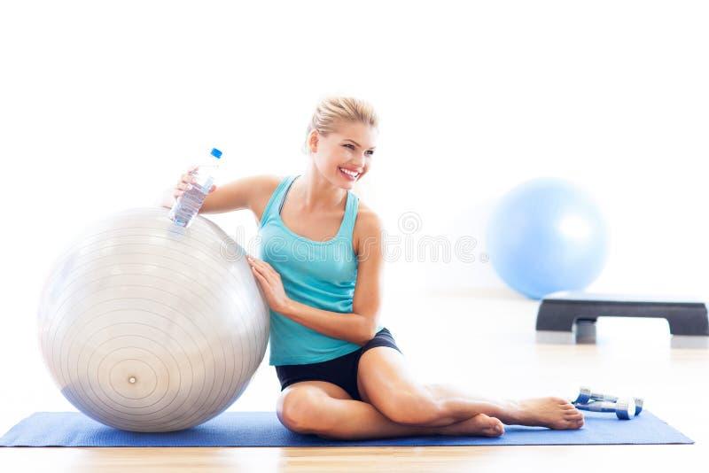 Femme s'asseyant avec la boule de forme physique image stock
