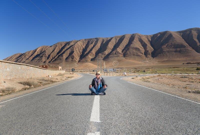 Femme s'asseyant avec la jambe croisée sur la route Fourchette dans la route morocco photographie stock