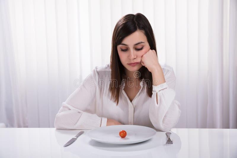 Femme s'asseyant avec le plat de Cherry Tomato images libres de droits