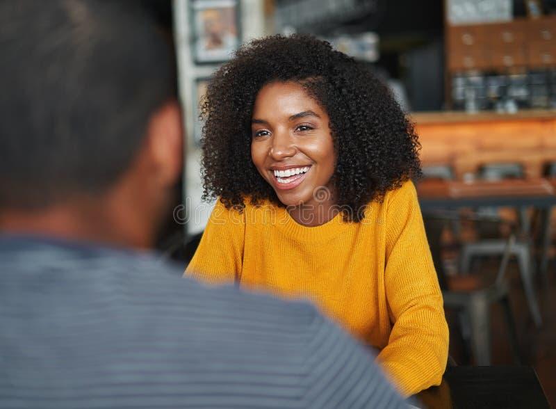Femme s'asseyant avec son ami en café images stock