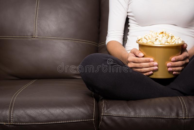 Femme s'asseyant avec un seau de maïs éclaté Aucun visage images libres de droits