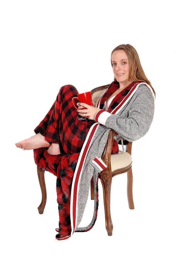 Femme s'asseyant avec une grande tasse de café image stock