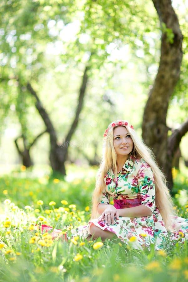 Femme s'asseyant dans l'herbe images libres de droits