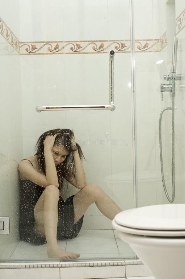 Femme s'asseyant dans la douche photo stock