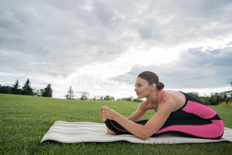 Femme s'asseyant dans la pose de yoga photographie stock