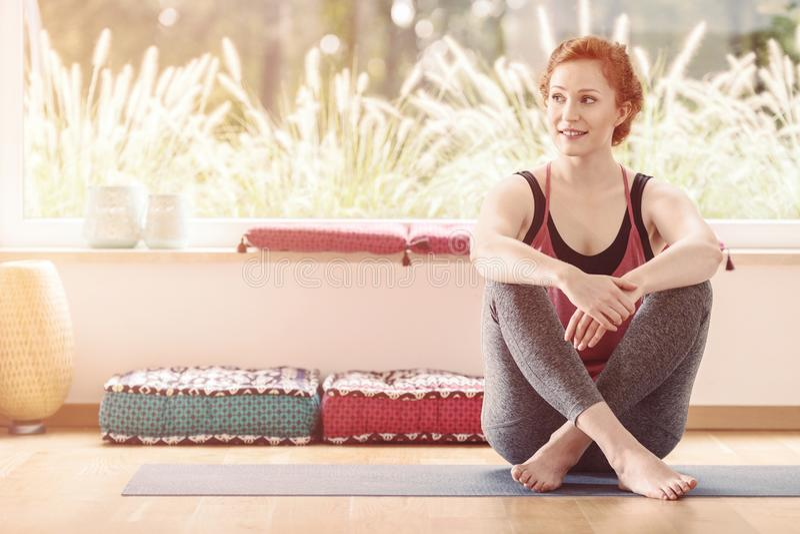 Femme s'asseyant dans la salle de classe de yoga photo libre de droits
