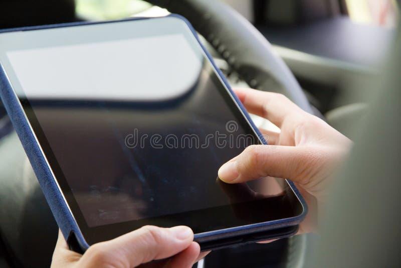 Femme s'asseyant dans la voiture et à l'aide du comprimé numérique image libre de droits