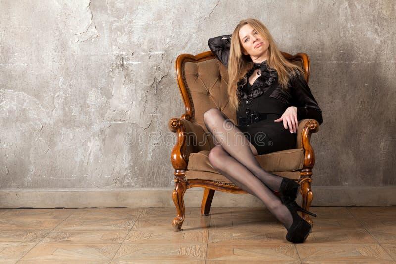 Femme s'asseyant dans le fauteuil photo stock