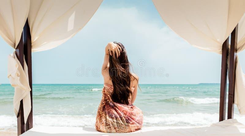 Femme s'asseyant dans le lit de plage regardant la mer images libres de droits