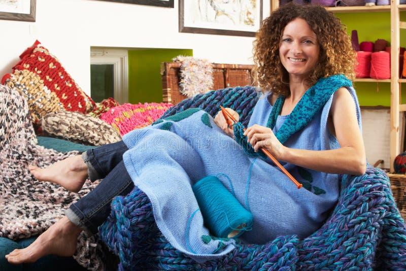 Femme s'asseyant dans le tricotage de présidence image stock