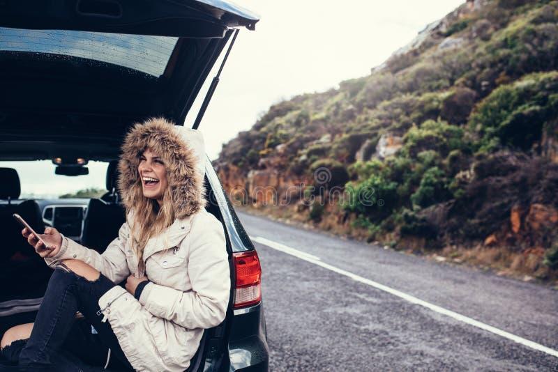 Femme s'asseyant dans le tronc de voiture avec un téléphone intelligent image libre de droits