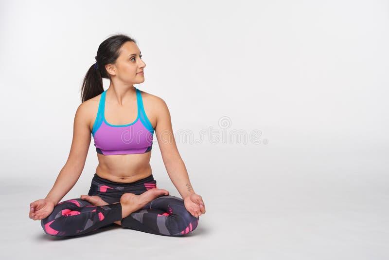 Femme s'asseyant dans le yoga Padmasana, pose de lotus photos libres de droits