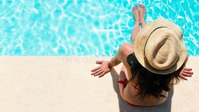 Femme s'asseyant dans une piscine photo libre de droits