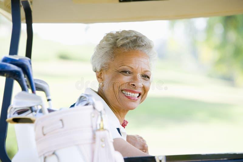 femme s'asseyant de verticale de golf de chariot photographie stock libre de droits