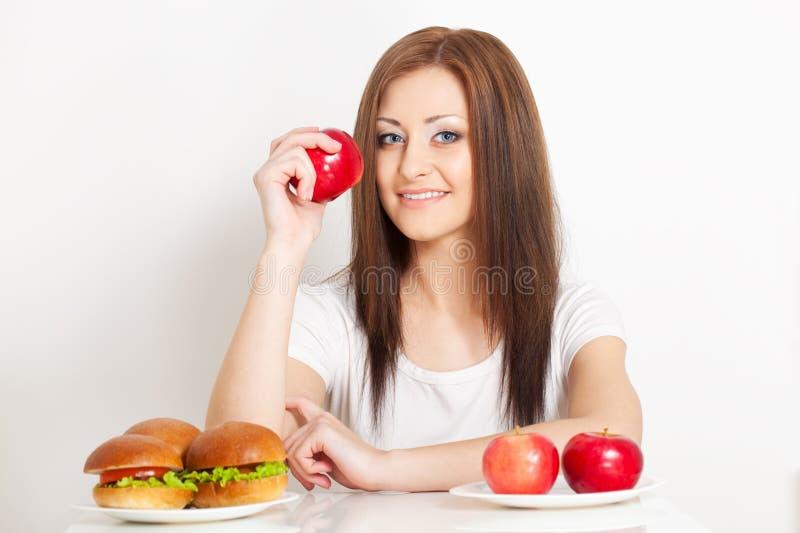 Femme s'asseyant derri?re la table avec la nourriture image stock