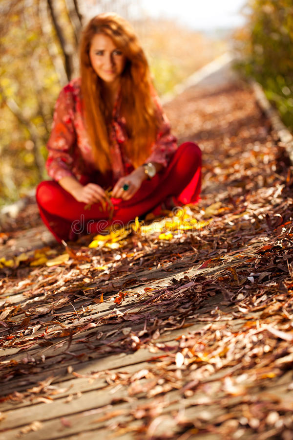 Femme s'asseyant en Autumn Nature - hors focale photos stock