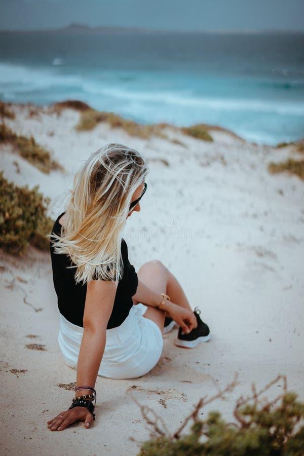 Femme s'asseyant en dune de sable blanche avec le paysage atlantique de littoral Ressacs frappant la côte à l'arrière-plan Sao Vi photos stock