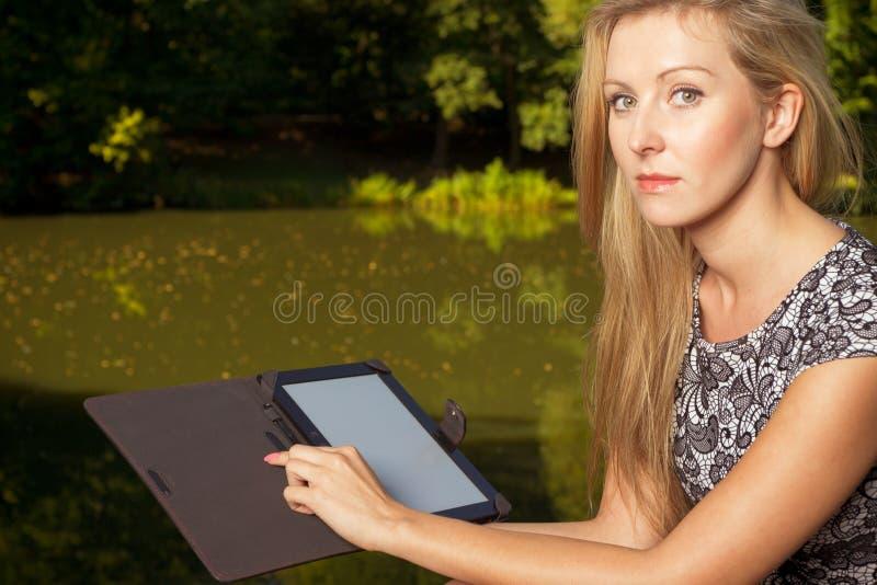 Femme s'asseyant en parc, détendant et à l'aide du comprimé image stock