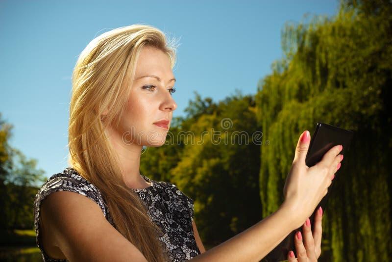 Femme s'asseyant en parc, d?tendant et ? l'aide du comprim? photo libre de droits